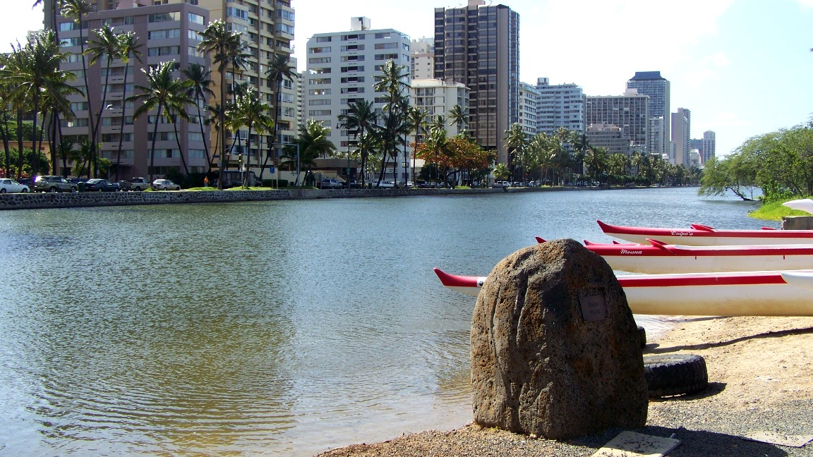 A special stone and canoes line the bank on the 'mauka' side with Waikiki condo's on the 'makai' side