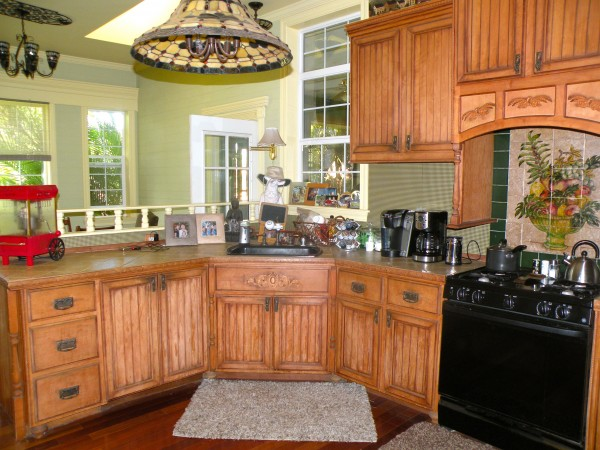 Kitchen has custom cabinetry with carved trim and hand finished stain.