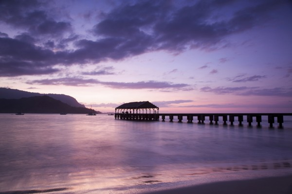 The Hanalei Bay pier at sunset in Kauai.
