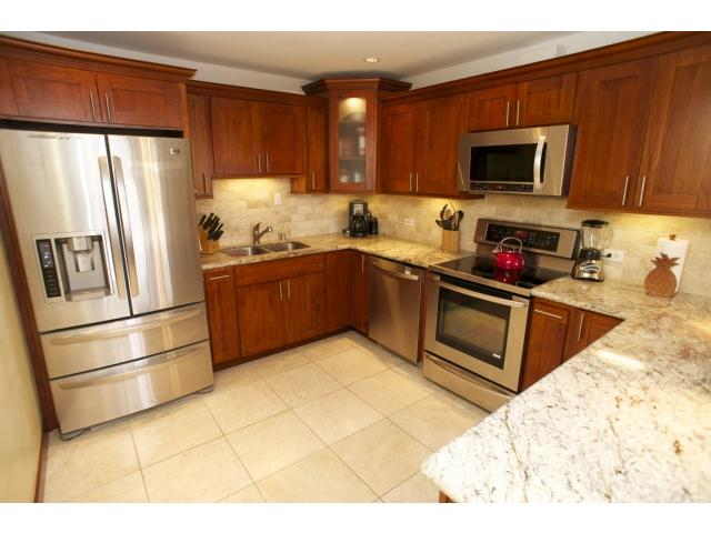 Elegantly upgraded kitchen with granite and travertine flooring.