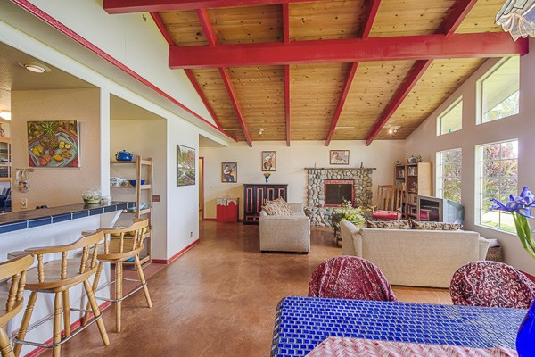 The spacious great room in this North Kohala home features a fireplace and stunning ocean views