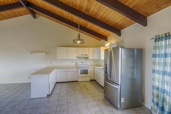 The kitchen features lots of counter space and a stainless steel refrigerator