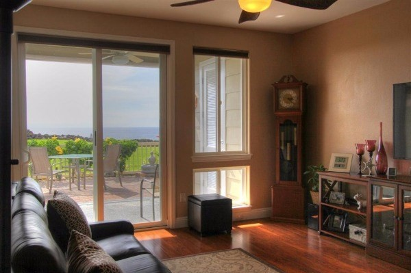 Living room with view to large, partially covered lanai and ocean beyond