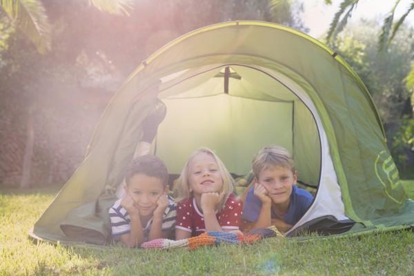 Portrait of three children lying in garden tent