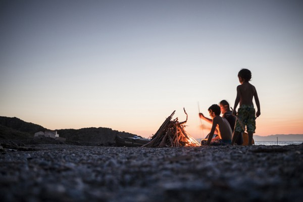 a man and two boys lighting a fire at the beach