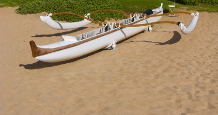 11949651 - white outrigger adventure canoe on beach sand