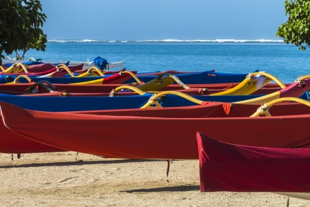 19879236 - colorful group of outrigger canoes at the shore